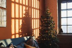 Vintage christmas interior with a christmas tree, bookcase, sofa, posters, photos and lettering in frames against the. Orange wall in the sunlight royalty free stock photography