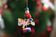 Wooden Christmas Carousel Ornament. Wooden Christmas tree ornament of a smiling child riding a carousel horse Royalty Free Stock Photo