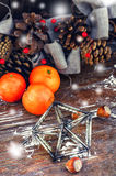 Vintage Christmas ornament toy octahedron. Woven Christmas wreath decorated with cones on background of ripe tangerines Royalty Free Stock Photography