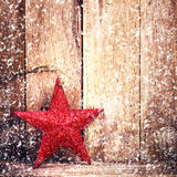 Vintage Christmas ornaments on wooden background with falling white snowflakes. Rustic Christmas Decoration. Old fashion Red Star. Vintage Christmas ornaments on stock photography