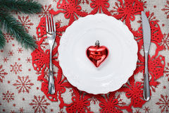 Vintage Christmas plate on holiday background with red heart. Canvas background with red glitter snowflakes. Xmas card. Happy New Year. Space for text Stock Photos