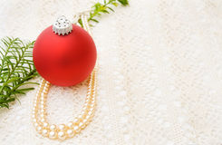 Vintage Christmas with red bauble and pearls. Celebrating vintage Christmas with traditional red bauble and old pearls over handmade lace Royalty Free Stock Images