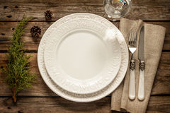 Vintage christmas table - empty white plate from above on wood. Vintage or rustic christmas table setting from above. Elegant empty white plate, cutlery on linen Stock Photo