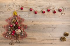 Vintage Christmas tree with burlap balls, cones, wooden sticks and red apples on beige wood background. Royalty Free Stock Photo