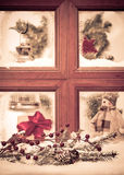 Vintage Christmas Window. With snowy scene, focus on fir cone and branch in front of window Stock Photo