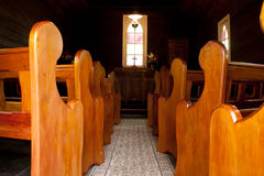 Vintage church aisle with pews and altar. A vintage colonial church aisle with wooden pews and altar with cross and stained glass window Royalty Free Stock Image