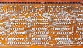 Vintage circuit board with soldering trace. Backside brown electronic chip retro style design. Macro view, shallow depth Royalty Free Stock Photography