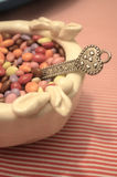 Vintage Circus Baby Shower Treats. Chocolate covered sunflower seeds in antique bowl with pewter teaspoon with heart handle Stock Photo