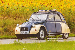Vintage Citroen 2CV in front of a field with blooming sunflowers Royalty Free Stock Images