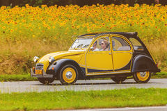 Vintage Citroen 2CV in front of a field with blooming sunflowers Royalty Free Stock Photography