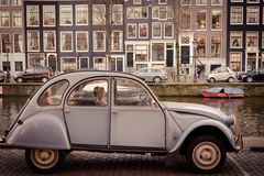 Vintage Citroen 2CV parked along a canal in Amsterdam Netherlands. March 2015. Landscape format stock photos
