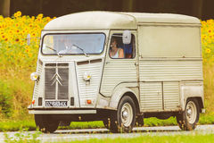 Vintage Citroen HY in front of a field with blooming sunflowers Stock Photos