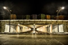 Vintage city bridge street tunnel with semi trailers at night. Dark and gritty vintage city bridge street tunnel with semi trailers at night Royalty Free Stock Photo