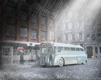 Vintage City Bus, Man, Rain. A vintage city bus is in a downpour rain storm. A businessman is holding a red umbrella. The main is waiting at the bus stop royalty free stock photography