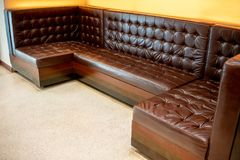 Vintage classic brown leather sofa on white floor against yellow royalty free stock photos