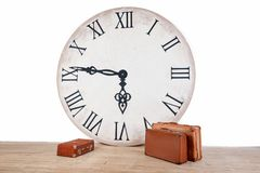 Vintage classic brown leather suitcases and big clock. World time in interior concept. Vacation travel holiday Stock Photo