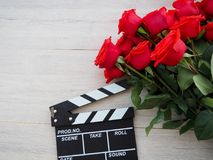 Vintage classic clapperboard on brown wooden table whis red roses Stock Images
