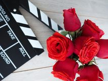 Vintage classic clapperboard on brown wooden table whis red roses Royalty Free Stock Images