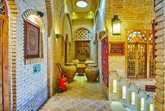 The vintage clay jars in carpet store, Shiraz, Iran. SHIRAZ, IRAN - OCTOBER 14, 2017: The corridor of old carpet store is decorated with vintage clay jars and royalty free stock photos