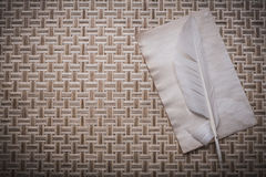 Vintage clean sheet of paper plume on wicker wooden matting Royalty Free Stock Photography