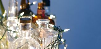 Vintage clear glass liquor bottles with Christmas lights. Calgary, Alberta, Canada Royalty Free Stock Images