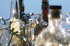Vintage clear glass liquor bottles with Christmas lights closeup Royalty Free Stock Photos