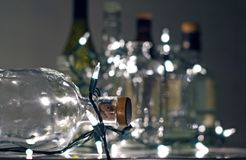Vintage clear glass liquor bottles with Christmas lights. Calgary, Alberta, Canada Royalty Free Stock Image
