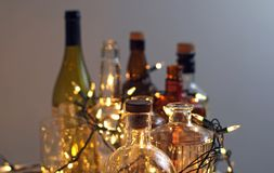 Vintage clear glass liquor bottles with Christmas lights Royalty Free Stock Photography
