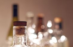 Vintage clear glass liquor bottles with cork in focus with plain. Background and Christmas lights. Calgary, Alberta, Canada Royalty Free Stock Images