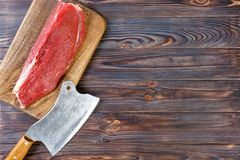 Vintage cleaver and raw beef steak on dark wooden background. copy space royalty free stock images
