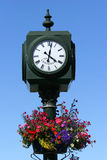 Vintage Clock. Old centenary metal street clock, with the time at just gone four o'clock, with colorful flowers in a metal pot below the clock face. Set against royalty free stock photography
