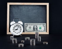 Vintage clock, blackboard, dollar bill, and coin towers on black Royalty Free Stock Photos