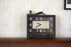 Vintage clock on the brown leather sofa Stock Photo