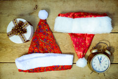 Vintage clock with christmas hats and present box Royalty Free Stock Images