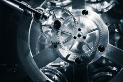 Vintage clock mechanism, close-up fragment. With shiny gears, blue toned photo royalty free stock photos