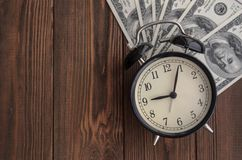 A vintage clock and money against a natural tree background. Tim. E is money Royalty Free Stock Images