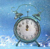 Vintage clock over blue ice bokeh background. new year concept. retro filtered with glitter overlay. selective focus Stock Photos