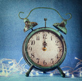Vintage clock over blue ice bokeh background and white garland. new year concept. selective focus Stock Photo