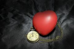 Vintage clock and red heart on black background ,Love and time concept in still life photography. royalty free stock images