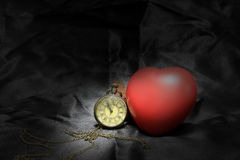 Vintage clock and red heart on black background ,Love and time concept in still life photography.  stock photos