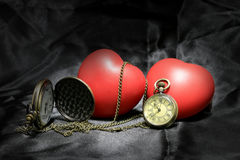 Vintage clock and red heart on black background ,Love and time concept in still life photography. royalty free stock photo