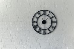 Vintage clock with Roman numeral. Wall clock-face dialrustical on white brick wall in the apartment stock photos