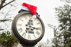 Vintage clock with text Merry Christmas New York and Santa Claus hat on them outdoor in winter. Park stock photo