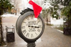 Vintage clock with text Merry Christmas New York and Santa Claus hat on them outdoor in central park. Vintage clock with title Merry Christmas New York and Santa stock photos