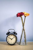 Vintage clock and vase flowers. Home decor : Vintage clock and vase flowers on wood desk Royalty Free Stock Photos