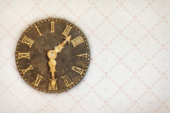Vintage clock on a wall with retro wallpaper Stock Photo