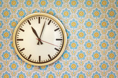 Vintage clock on a wall with retro wallpaper Royalty Free Stock Photo