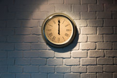 Vintage clock on a white brick wall. At 12:00 Royalty Free Stock Images