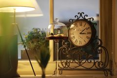 A vintage clock on a windowsill behind royalty free stock photography