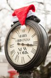 Vintage clock with writing Merry Christmas New York and Santa Claus hat on them outdoor in winter. Vintage clock with text Merry Christmas New York and Santa royalty free stock photos